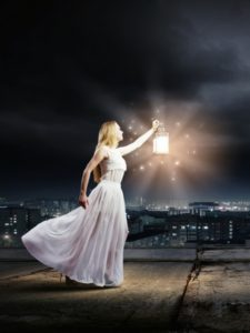 woman with a lantern shining her light in a city